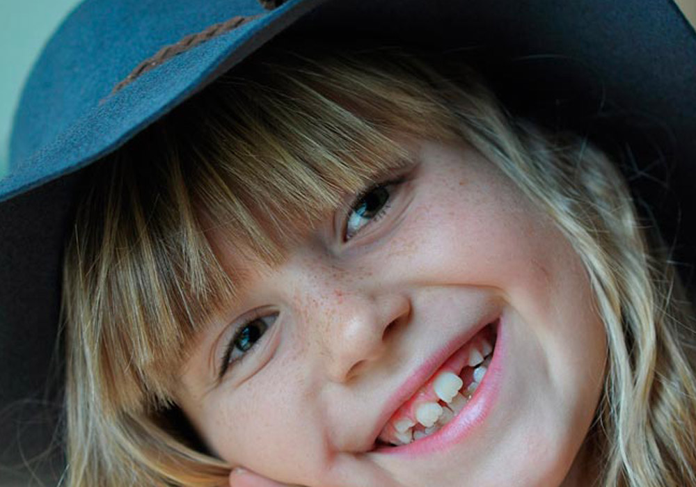 close up of child smiling in a hat