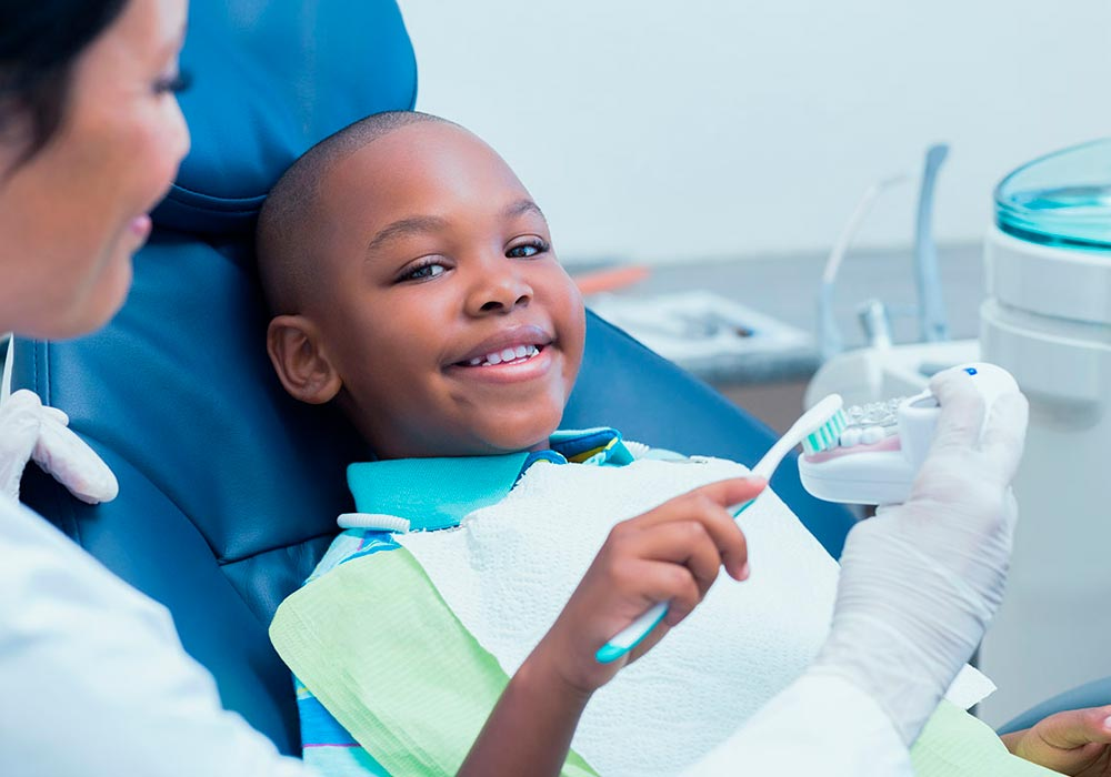 dentist showing a child how to brush teeth