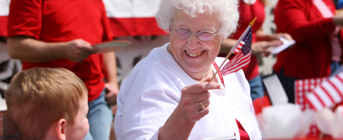 photo of senior woman waving an American flag at a 4th of July event and smiling at her grandson