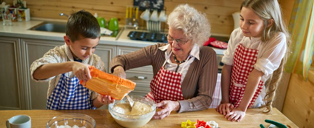 photo of grandmother making cookies with her grandchildren
