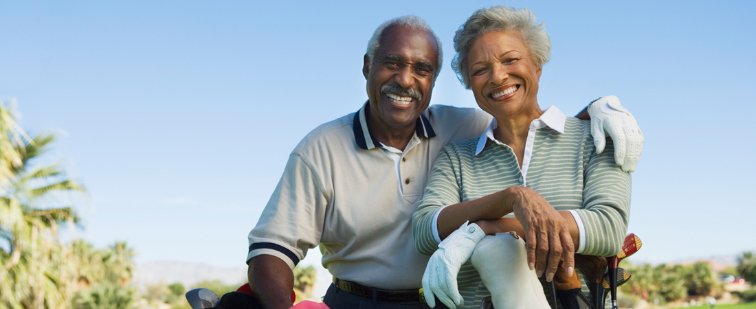 photo of smiling senior couple with their golf clubs