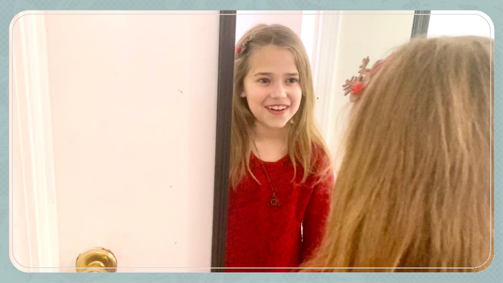 little girl smiling in front of mirror