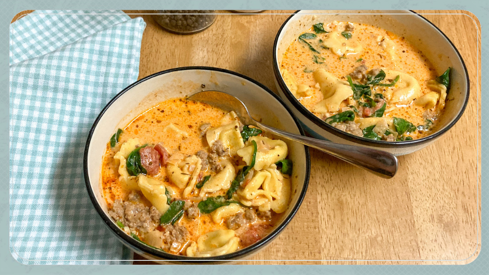 Two bowls of tortellini soup on wooden table