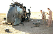 Local safety officials inspect the wreckage of an Army UH-60 Blackhawk crash at Tallil Air Base, Iraq.  All four Soldiers on board were rescued from the helicopter by members of Tallil's 407th Air Expeditionary Group and 407th Expeditionary Medical Squadron. Photo by A1C Jeff Andrejcik.