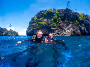 Two international guests with peace symbol whilst floating at the surface after a fun dive with Submariner Diving Center