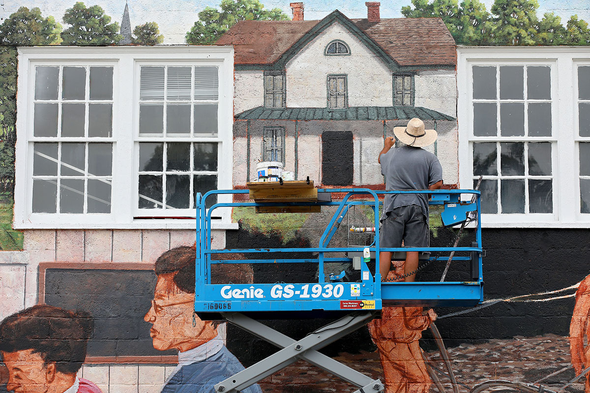 Artist Michael Rosato paints in TC Walker's home at the top on the mural he's painting in downtown Gloucester