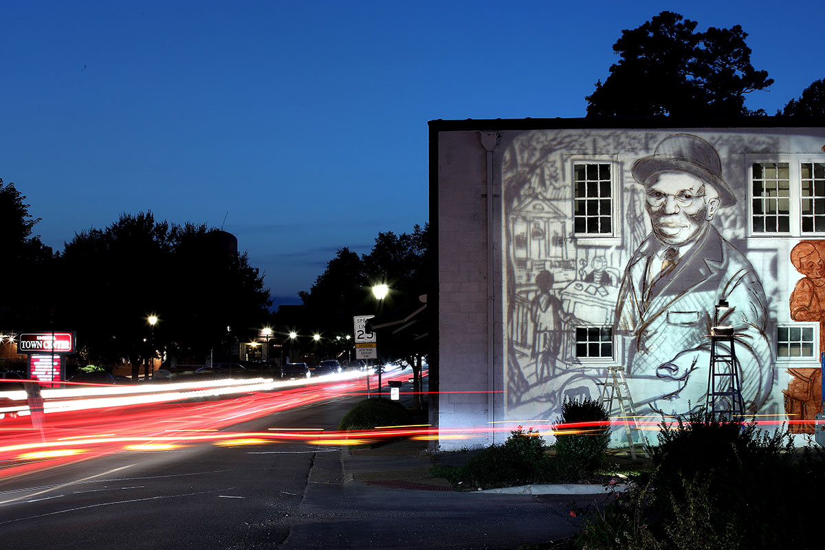 Artist Michael Rosato paints an outline of TC Walker projected on the building in downtown Gloucester that will soon have a mural dedicated to the iconic lawyer