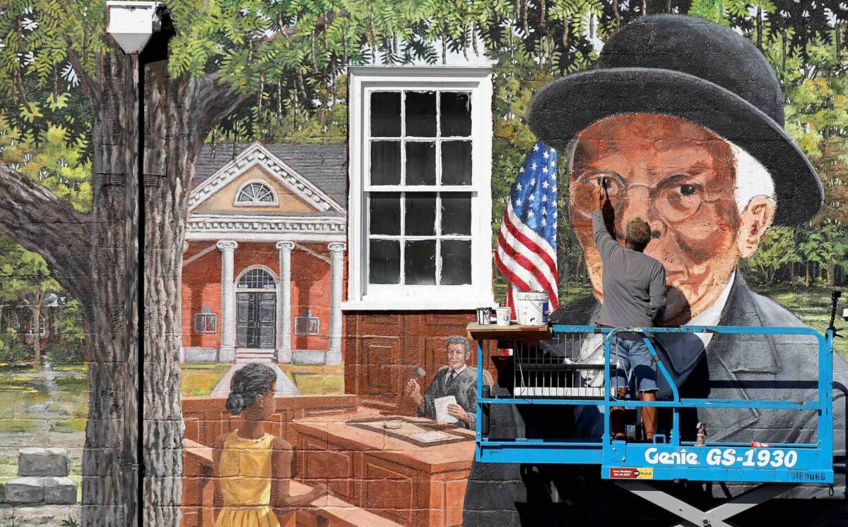 Artist Michael Rosato paints in the details of TC Walkers face on the mural in downtown Gloucester