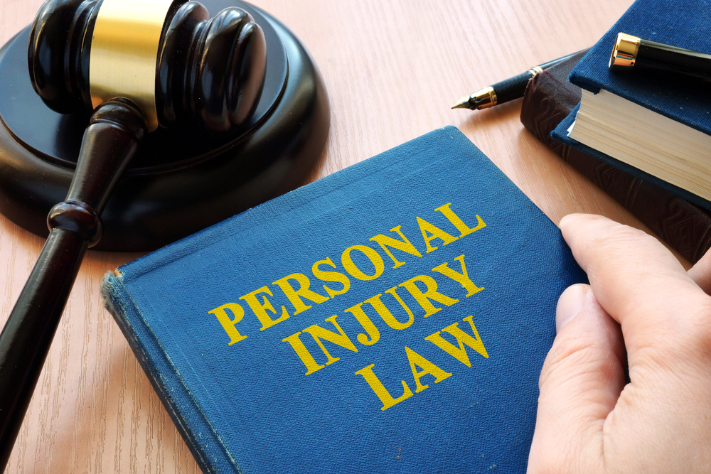 A personal injury law book and gavel sit on a desk while Hayhurst Law explains the taxation of personal injury settlements