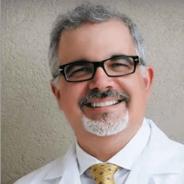 Dr. Al Castenada, sporting glasses, a yellow tie, white shirt and coat, smiling at the camera
