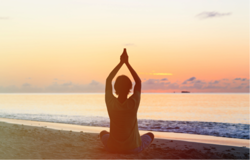 A woman meditates on a beach during sunset to aid in her treatment at a women's drug rehab center in Vancouver.