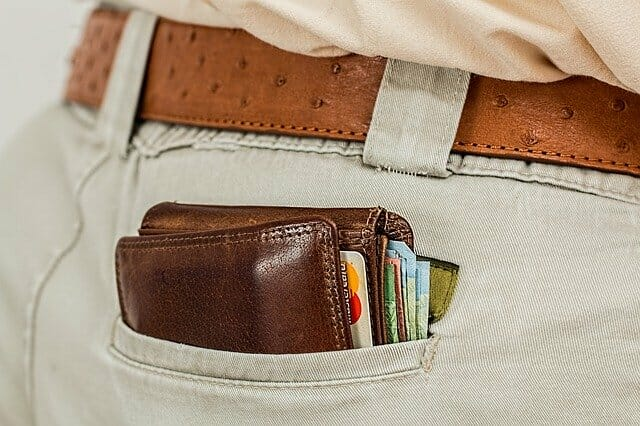 man's back pocket with wallet and money in it