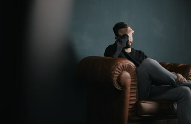 man sitting on couch worried if he can be sued after a car accident
