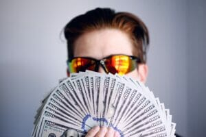 man with sunglasses holding up hundred dollar bills