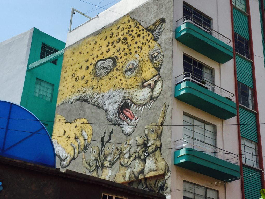 Mural of a jaguar and rabbits. The jaguar represents the Mexican government. On eo fthe rabbits is wearing a black armband with teh number 43 representing the disappearance of 43 students kidnapped in 2014