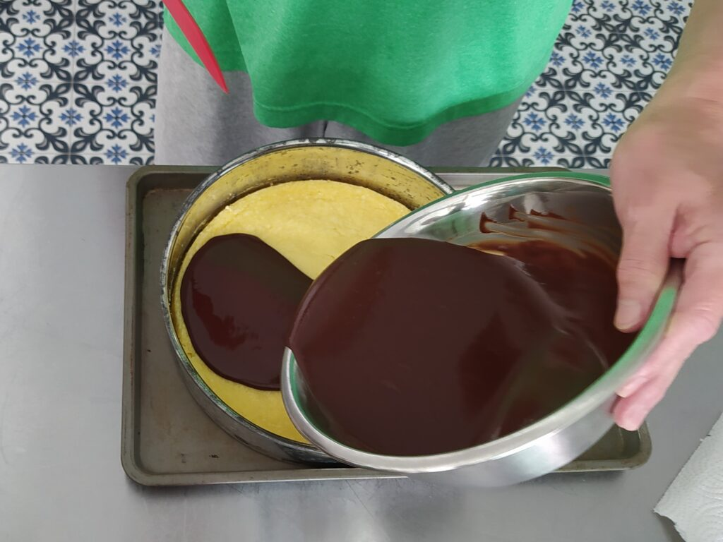 Pour the ganache over the cheesecake