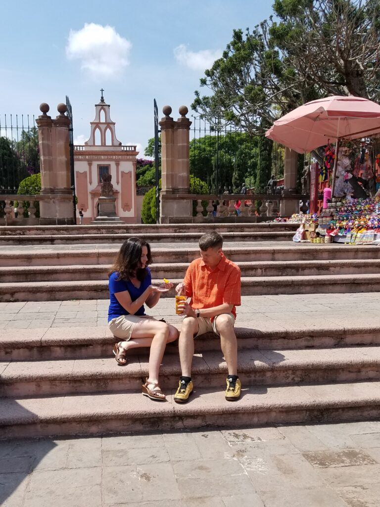 Eating mangos outside Mausoleo de la Corregidora, Queretaro, Mexico