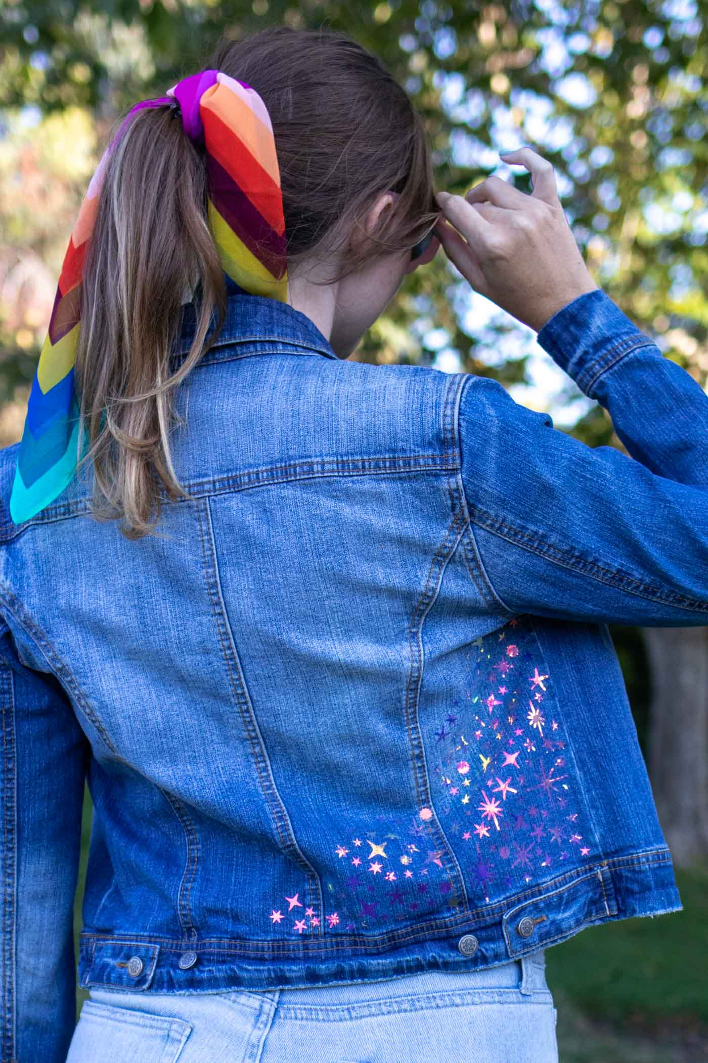 DIY Celestial Holographic Jacket Detail // How to use heat transfer vinyl or holographic iron-on vinyl to make a starry design to update a denim jacket! Download these FREE SVG files for Cricut to make a 90s-inspired holographic denim jacket for the fall // #ad #handmadewithjoann #diystyle #womensfashion #fabricdiy #irononvinyl #holographic #iridescent #freetemplate
