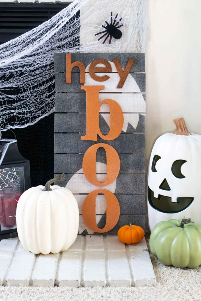 """""""Hey Boo"""" Punny Halloween Sign DIY // Make a fun wooden Halloween sign with a punny saying to decorate your home for Halloween! Decorate your front door, fireplace or other corner of your home using supplies from @joann given a makeover with the NEW @rustoleum Imagine collection, including glitter spray paint #ad #handmadewithjoann #halloween #halloweendiy #homedecor #halloweendecor #painting #spraypaint"""