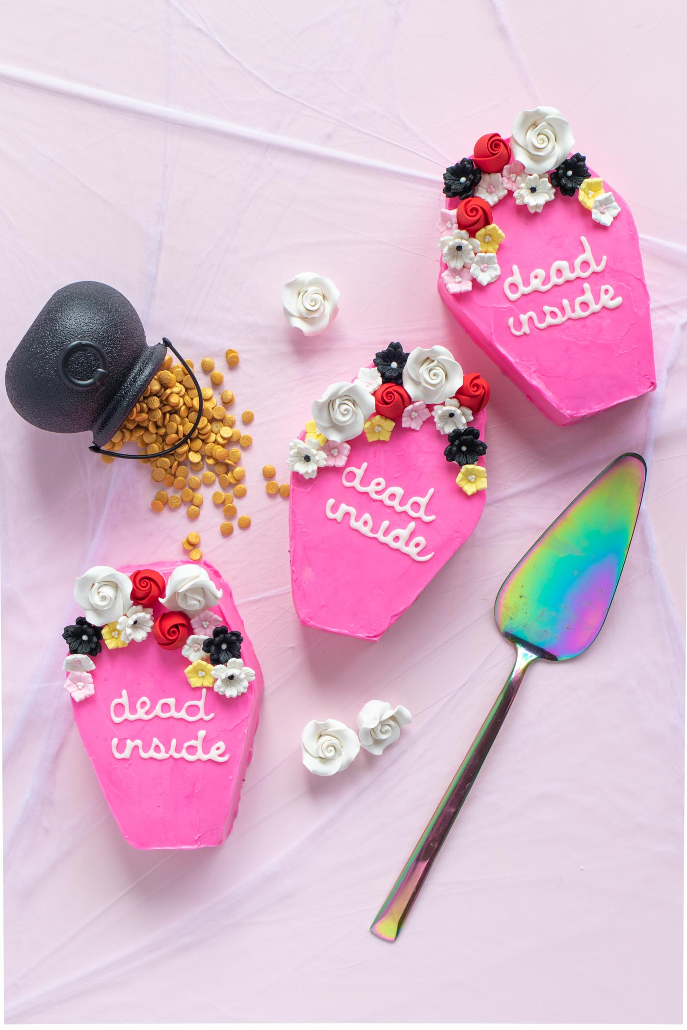 """Pink Mini Coffin Cakes for Halloween / Cute mini cakes shaped like coffins, decorated with pink frosting! Add """"dead inside"""" in royal icing and icing flowers for a fun Halloween treat #halloween #halloweendessert #halloweentreat #coffin #frosting #cakedecorating #holidaybaking #halloweenbaking"""