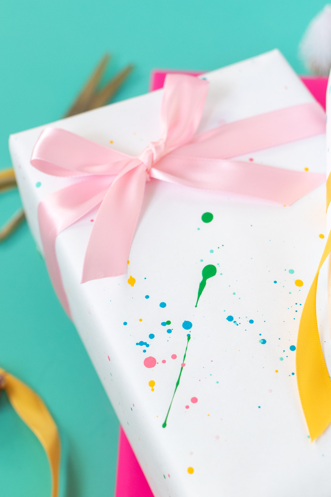 DY Splatter Painted Gift Wrap // Make your own wrapping paper with this simple splatter technique using colorful supplies from @joann! Add 80s and 90s-inspired splatter designs to plain paper for fun DIY gift wrap for Christmas and beyond! #ad #handmadewithjoann #giftwrap #diygiftwrap #wrappingpaper #splatterpaint #painting #rainbow