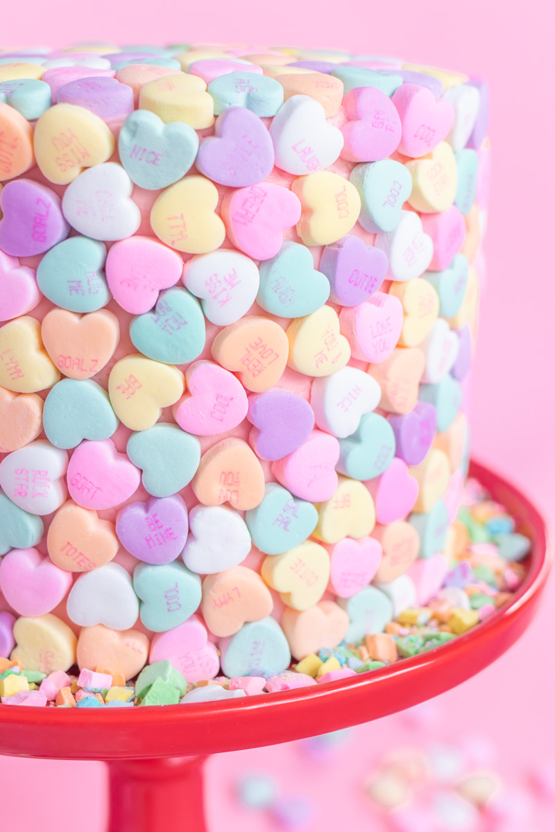 Valentine's Day Cake Idea // Conversation Heart Cake // This easy V-Day cake is as simple as using mini heart candies to cover the cake for a perfect Valentine's Day dessert! #cakedecorating #cakeideas #cakerecipes #valentinesday #galentinesday #valentinesdaydessert
