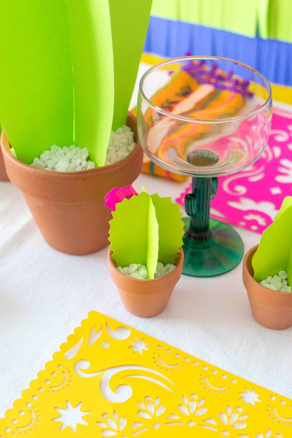 mini paper cacti in pots on tablecloth with glassware and paper placemats