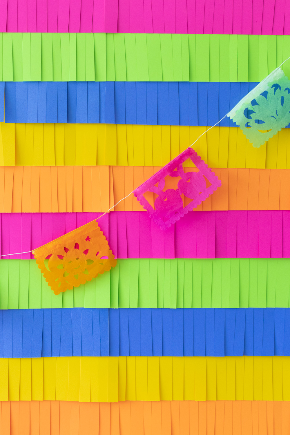colorful paper fringe backdrop with papel picado flags