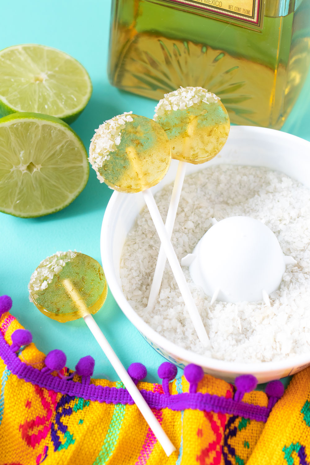 three margarita lollipops arranged in salt with bottle of tequila