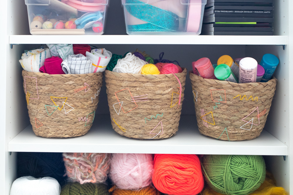 3 baskets filled with craft supplies on shelf in cabinet