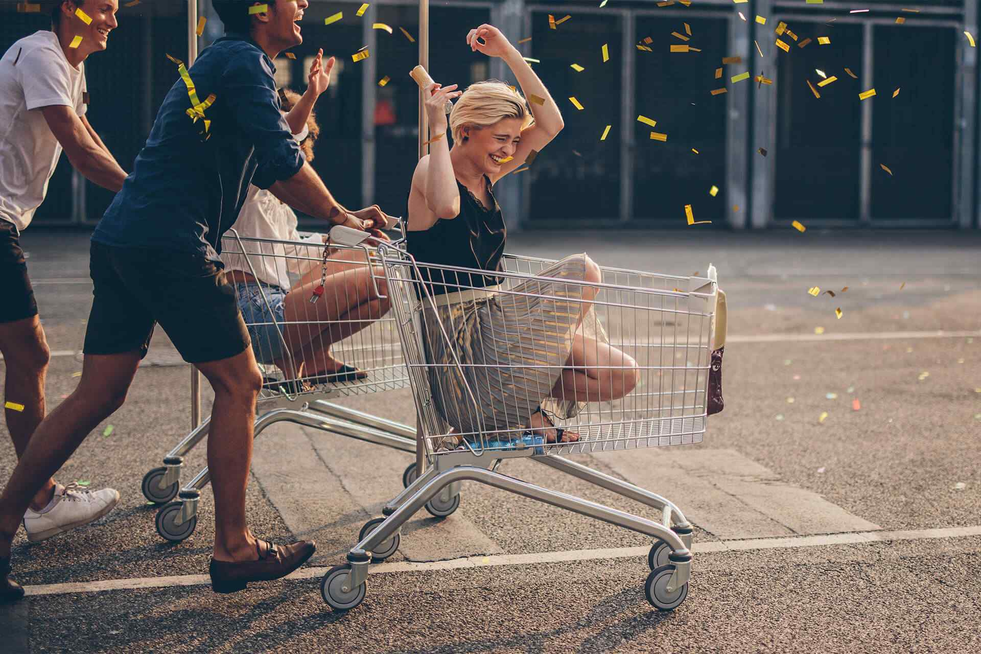 four young millennial friends having fun by playing with shopping carts; gold confetti is falling on them