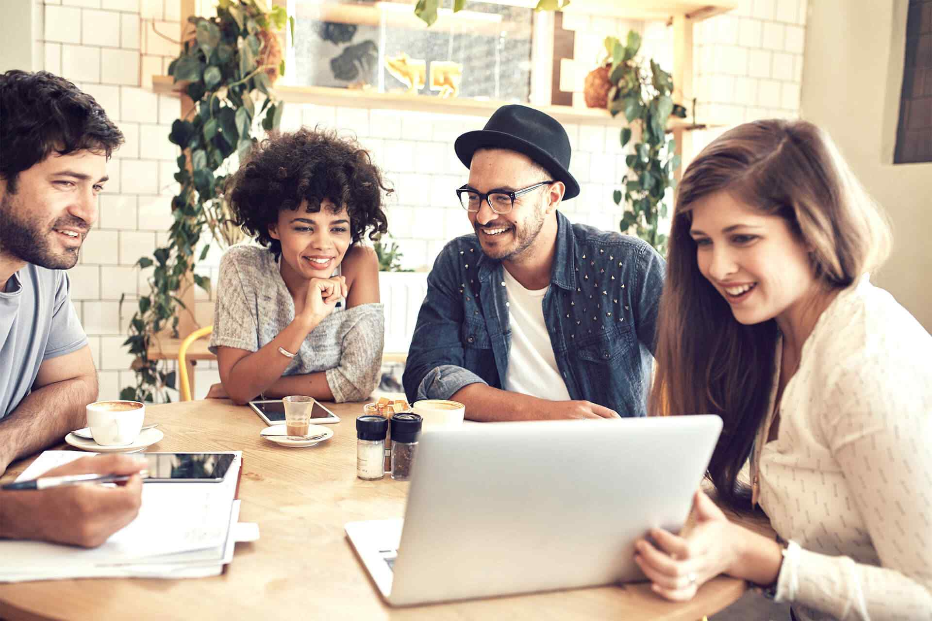 three young millennials smiling at a computer screen; one young millennial smiling at his coworkers' notes