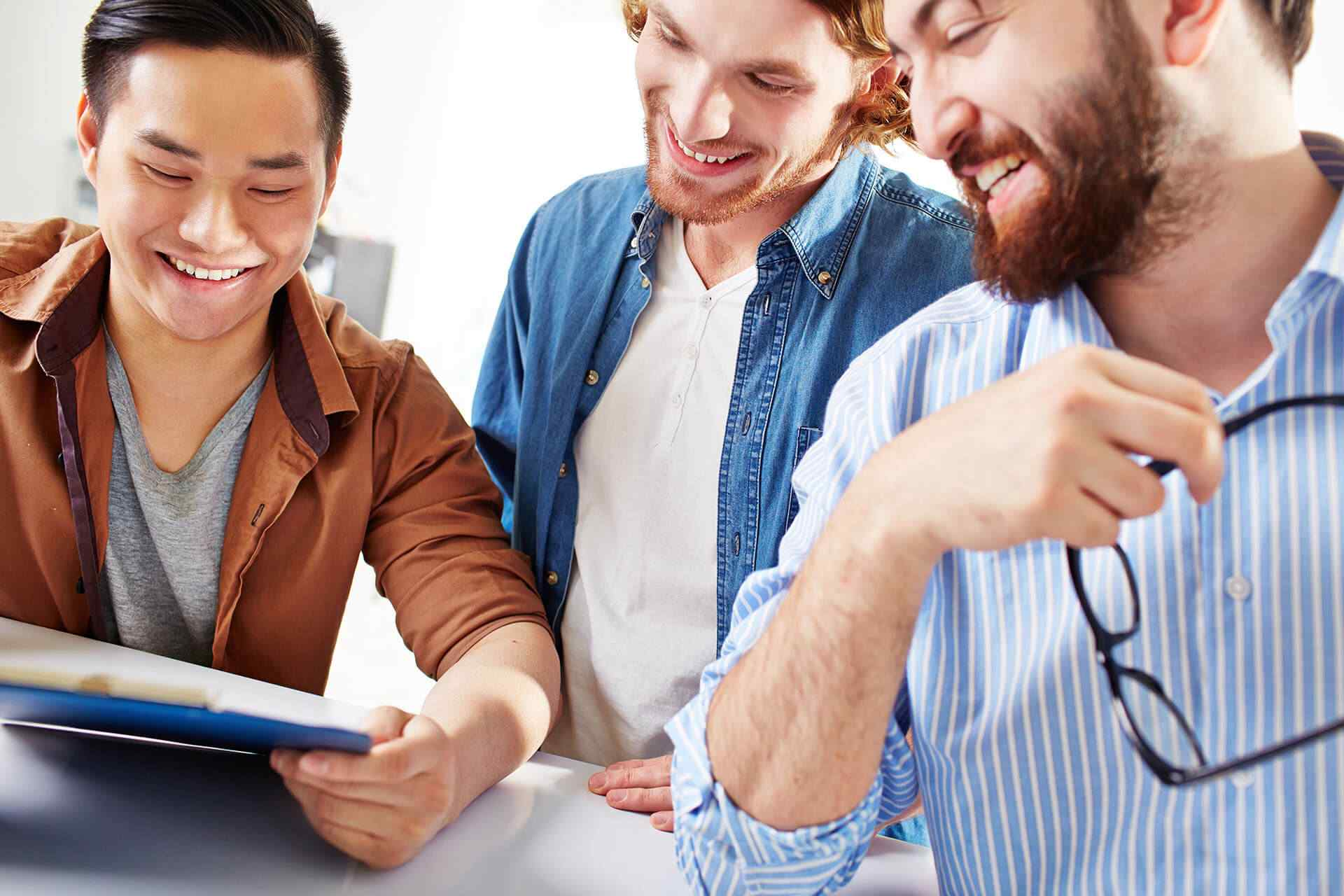 millenial men smiling at a document while in office space