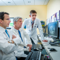 Thomas Clancy, M.D. (glasses), Brian Wolpin, M.D. and Richard Swanson, M.D. (grey hair). Leaders of our Pancreatic Biliary Center look over patient imaging in the physician workroom on Yawkey 7.