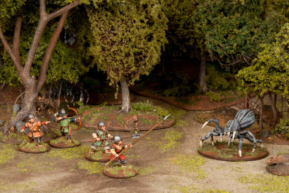 Halflings take on a miniature spider in this skirmish game setting