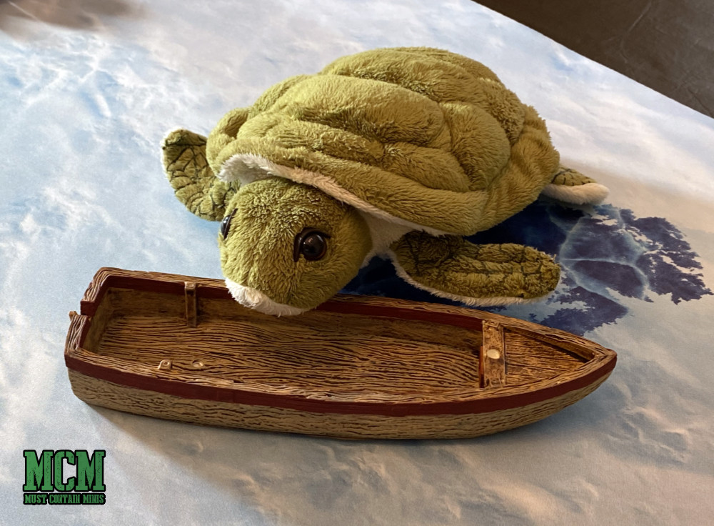 A Plush Turtle toy finds a boat in a frozen lake.