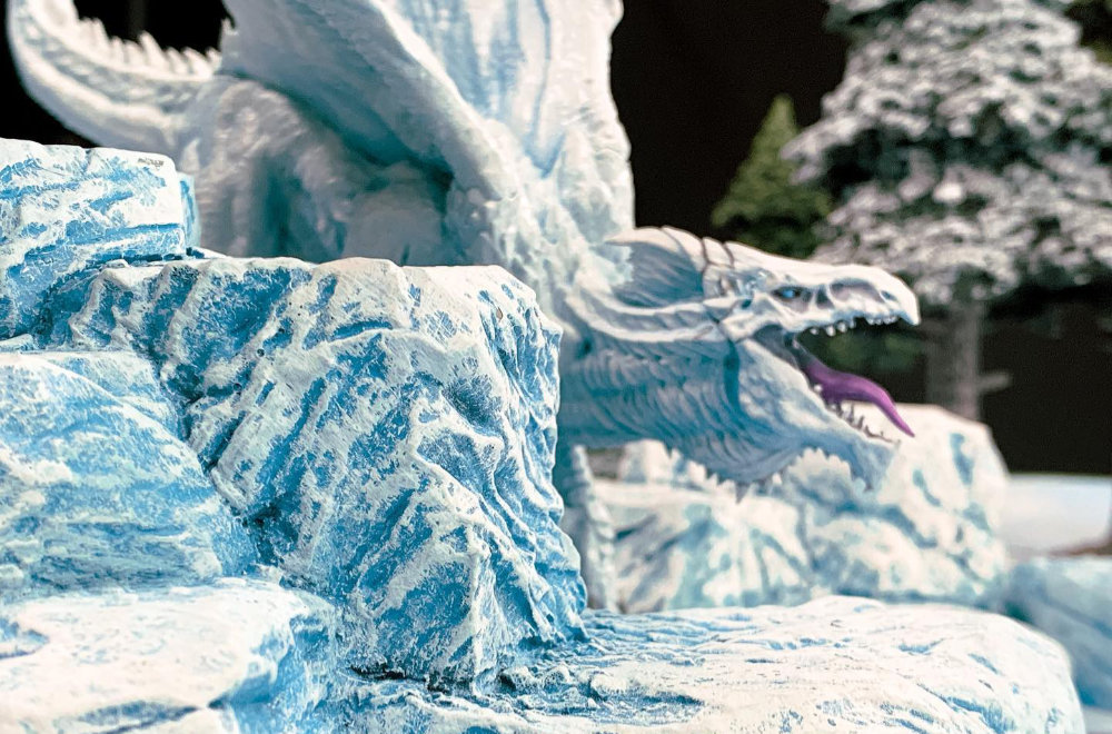 An Ice Dragon on a table with fantastic terrain for role playing games and miniature wargames.