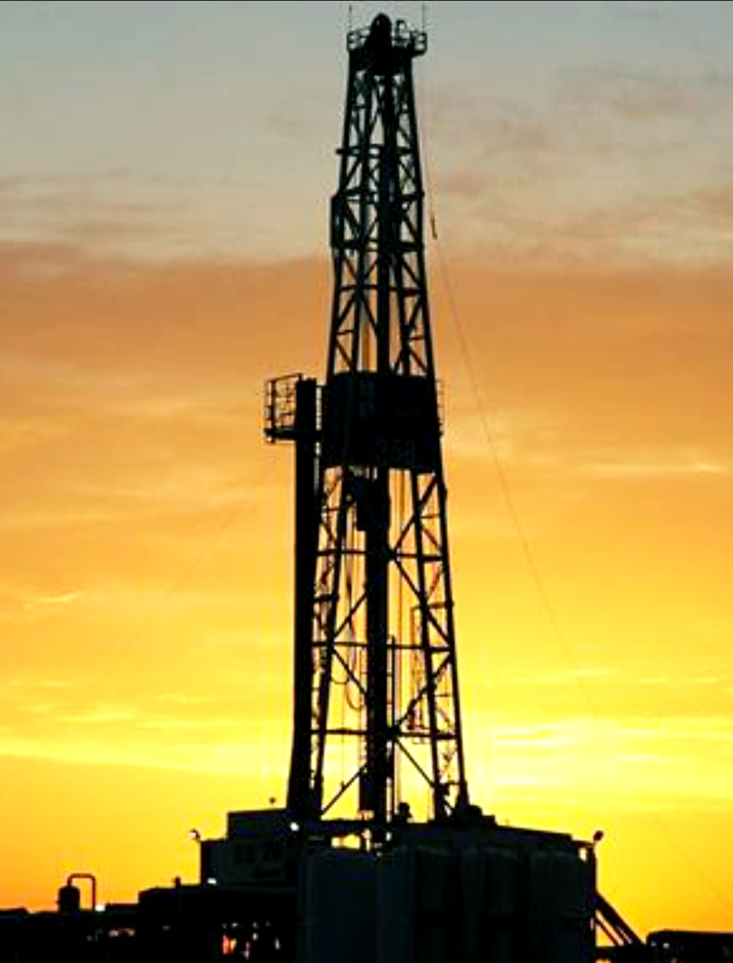 Oil & Gas Drilling Rig Image With The Sun Rising In The Background