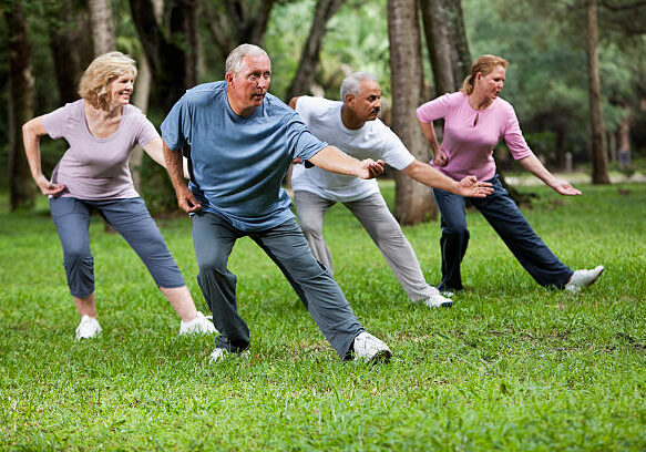 Multi-ethnic group of adults practicing tai chi in park.  Main focus on senior man (60s) in blue shirt.