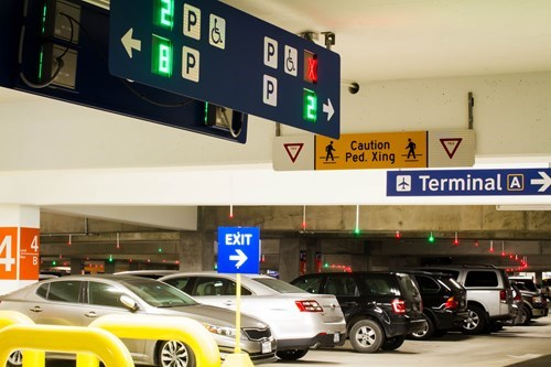 Cars in a garage with parking guidance lights and sign to Terminal A