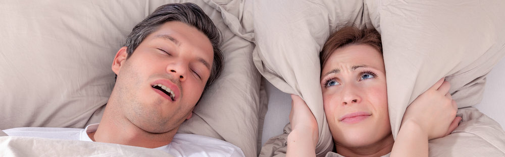 man snoring in bed with wife