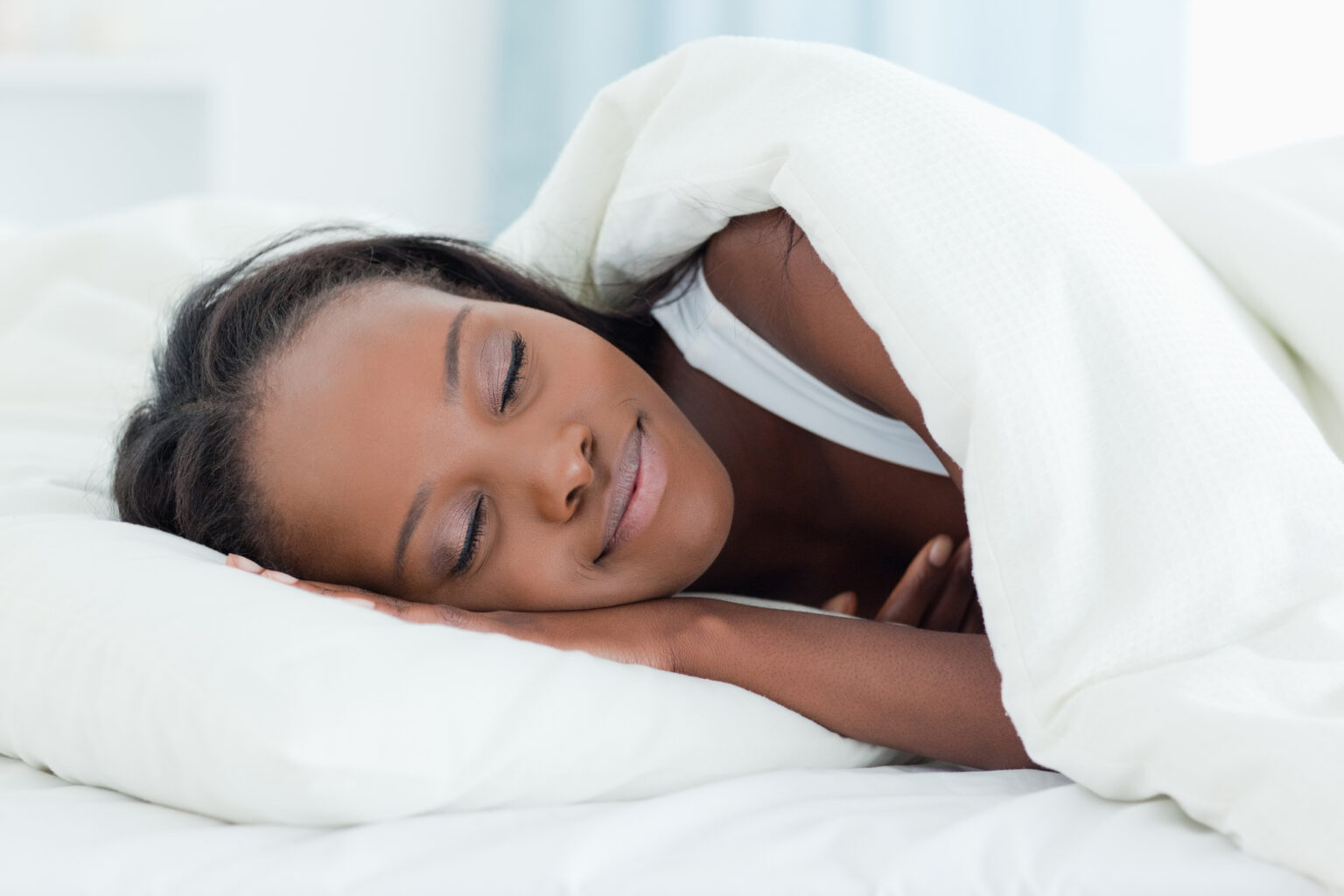 black woman sleeping in white bed