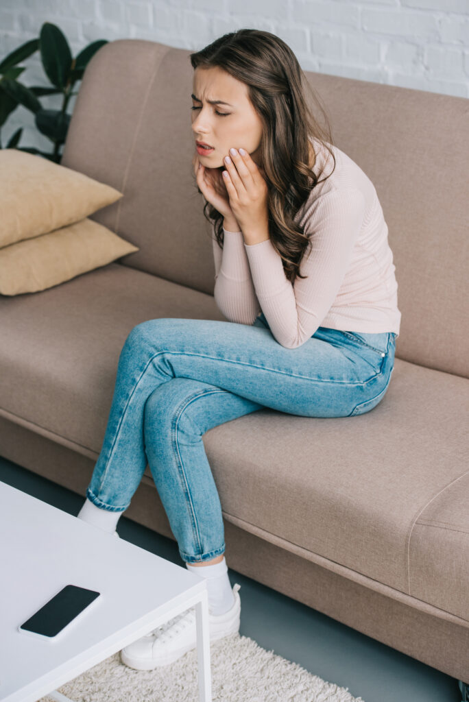 woman sitting on couch wincing in pain