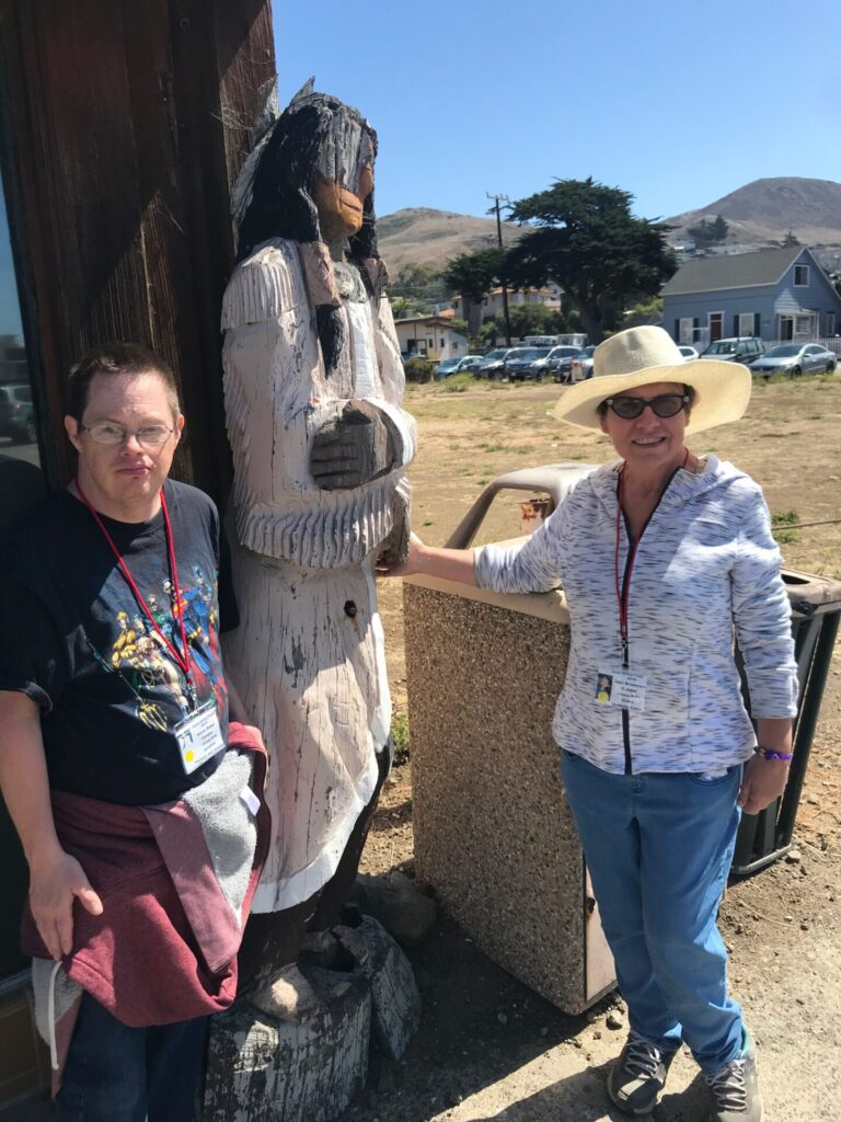 Two UCP members posing next to a wooden statue at Camp Kelley Creek