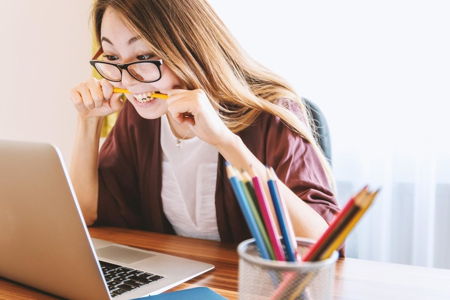 stressed out woman biting a pencil while working