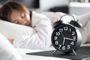 woman sleeping on bed next to clock