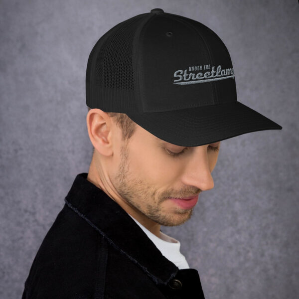 under the streetlamp hat side view all black