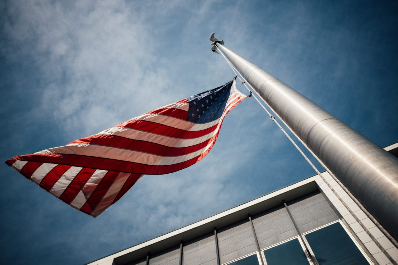 Closeup of flag pole with American flag waving in wind