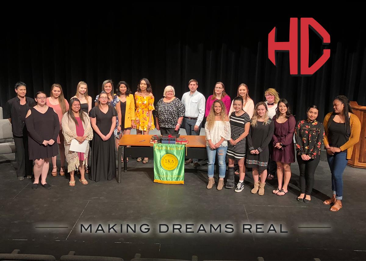Image of group of people posing behind green and gold Sigma Kappa Delta banner, with red letters HC in background