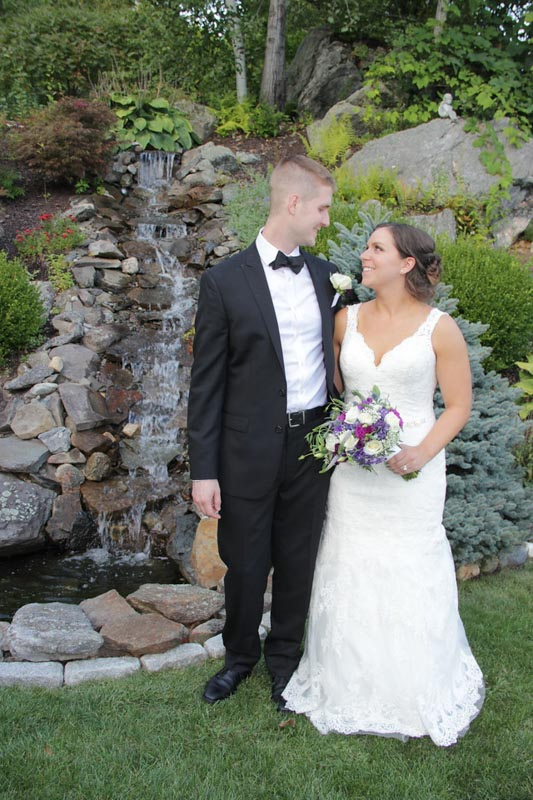Bride and Groom Standing in Front of a Waterfall